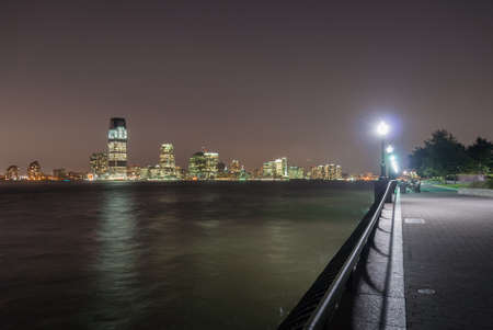 Battery Park in New York City at night with a view of Jersey City, New Jersey.