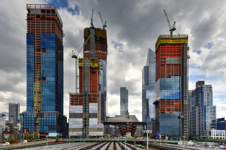 View of the Hudson Yards train depot and building development seen from the High Line, an elevated green urban park running along old rail track lines in New York City.