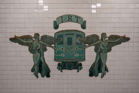 New York City - April 20, 2018: IRT (Interborough Rapid Transit Company) New York City Subway sign at Grand Army Plaza Brooklyn, New York. Two trumpeting angels flanking an early 1900s train.