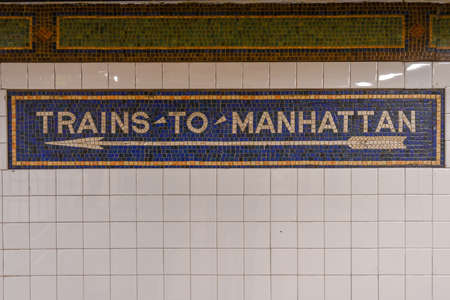 Trains to Manhattan mosaic arrow sign in the  NYC Subway.