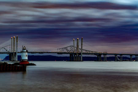 New and Old Tappan Zee Bridges coexisting across Hudson River with a dramatic sunset. Фото со стока