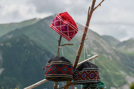 Hats for sale in the Mountain Panorama of Kazbegi, Georgia.