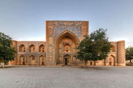 Madari Khan Madrassah boasts the perfectly decorated courtyard with the blue tiled traceries on the walls in Bukhara, Uzbekistan.