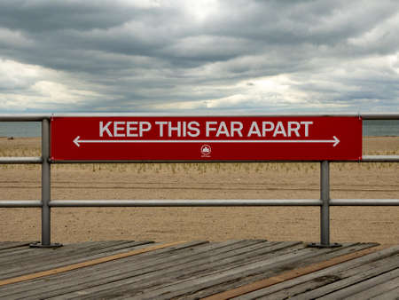 Sign for Social Distancing in a New York City Park on the boardwalk along Brighton Beach during the Coronavirus epidemic. Banco de Imagens