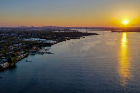 Aerial view of Queens in New York City at sunset with the George Washington Bridge in the background.