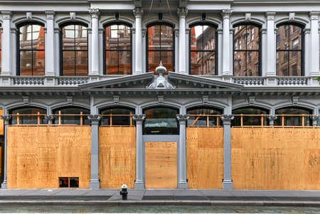 New York City, New York - June 11, 2020: Store closed during the COVID-19 pandemic, with boarded up windows to protect against looting as a result of anti-police brutality protests.