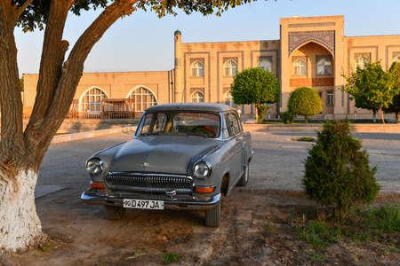Khiva, Uzbekistan - July 14, 2019: Classic Soviet car Volga - parked outside the city walls of the UNESCO site of Khiva, Uzbekistan.