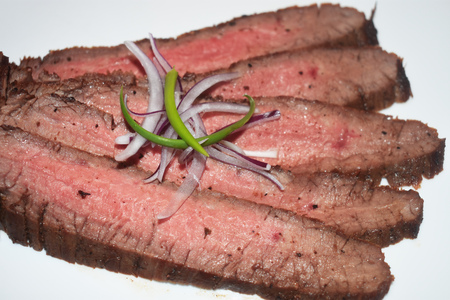 Broiled flank steak strips with onions and scallions
