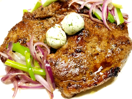 Grilled porterhouse steak topped with garlic butter