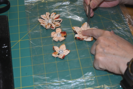Woman's hands putting final touches on handmade Kanzashi ornamental flowers using kimono material Banque d'images