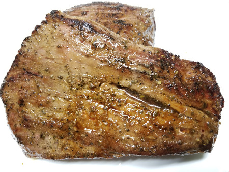 Grilled whole flank steak on a white background