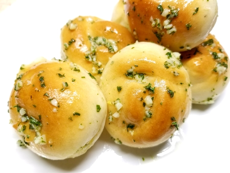 Delicious home made garlic knots on a white background