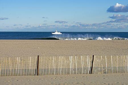 Heavy surf crashing into a sandy shoreline at Belmar Beach, New Jersey, USA, under a partly cloudy sky -05