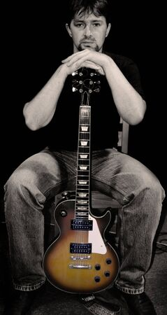 noire: Portrait of the guitarist on a black background. Color and computer processing