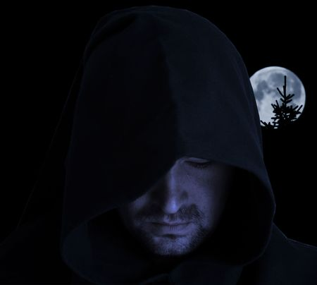 Man in an ancient hood on a full moon background Stock Photo
