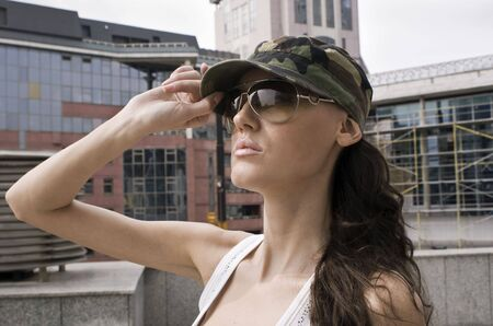 urbanistic: The young girl in a military peak-cap on a city landscape background   Stock Photo