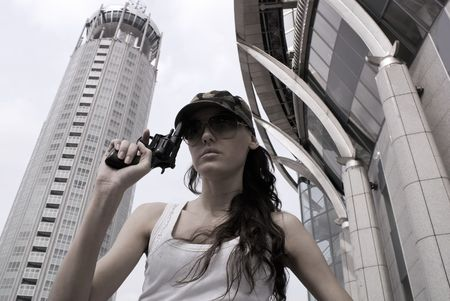 The young girl with a revolver on a city landscape background   photo