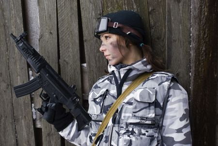 one armed: Girl in a camouflage with the gun in hands Stock Photo