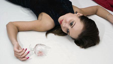 Young poisoned woman lying on the floor. Studio shot. photo