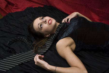 Young strangled woman on the floor. Studio shot. photo