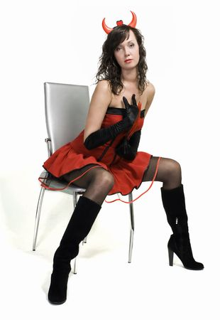 Beauty red devil girl sitting on a chair over white Stock Photo - 7495097