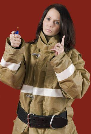 warns: Girl in fireman uniform warns: Be careful with fire! Stock Photo