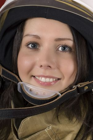 Portrait of a young smiling girl in a fireman`s helmet photo