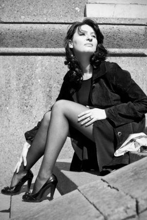 Beautiful italian woman sitting on stone steps photo