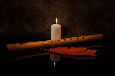 Still Life with flute, burning candle and red feather photo