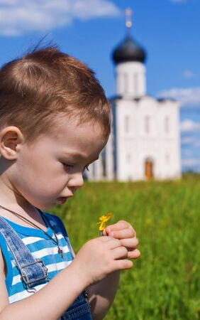 Little boy on a  orthodox church background. Church of the Intercession on the Nerl (Vladimir region of Russia)  Stock Photo - 7563195