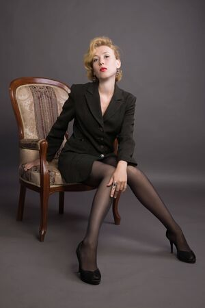 Beautiful young woman in a in a business suit sits in an armchair Stock Photo - 7569630