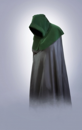 monjes: Niebla de crepuscular. Hombre en una capucha medieval y el manto en la niebla