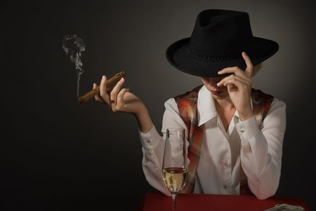Portrait of beautiful woman in a black hat with a cigar photo