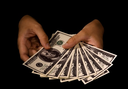cash on hand: womens hands with packs of dollars over black Stock Photo