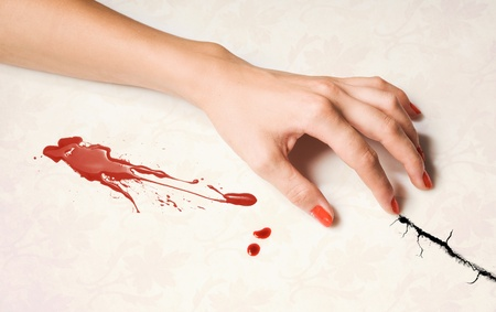 woman's hand and a drop of blood over white
