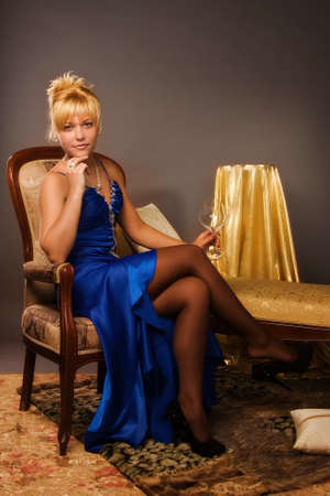 Aristocratic lady in a dark blue dress in a luxurious boudoir photo