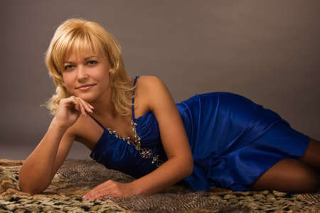 Aristocratic lady in a dark blue dress lying on the floor photo