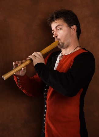 Man in a medieval suit plays a wooden flute photo