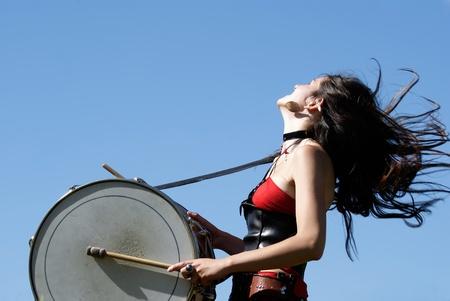 abito medievale: ragazza in un vestito medievale espressivo, suonando la batteria