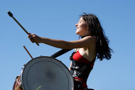 Expressive girl in a medieval dress playing the drums photo