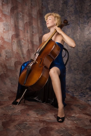 Pretty woman in evening dress playing cello  photo