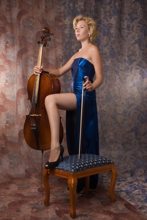 Attractive woman in evening dress posing with cello photo