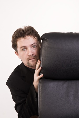 freaked: Frightened businessman hiding behind a chair  Stock Photo