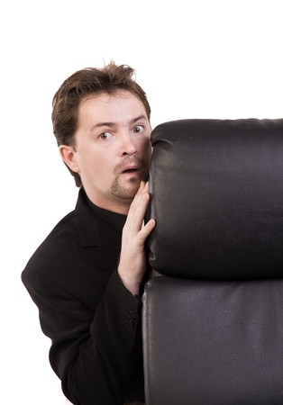 freaked: Frightened businessman hiding behind a chair