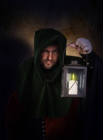 Night watchman in a medieval suit and hood with a lantern photo
