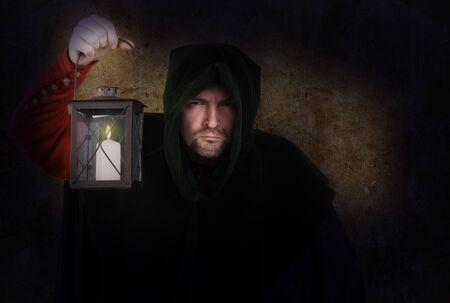 monjes: Vigilante nocturno en un traje medieval y capucha con una linterna