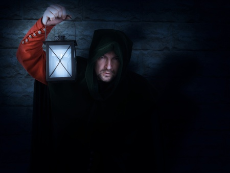 Night watchman in a medieval suit and hood with a lantern