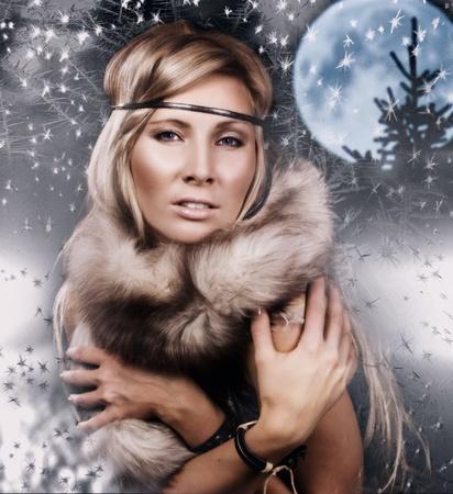 Snow Queen. Attractive girl in a fur cape on a snow winter landscape photo