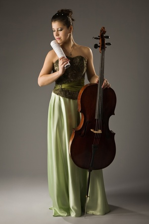 Beautiful woman in evening dress with cello and notes photo