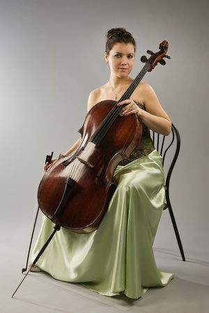 violoncello: Attractive woman in evening dress with cello Stock Photo
